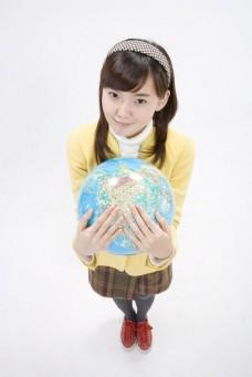 双手抱着地球仪的可爱女生图片