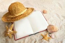 沙子上的书本与帽子图片