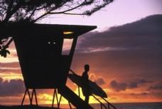 黄昏下拿着冲浪板的人物图片图片