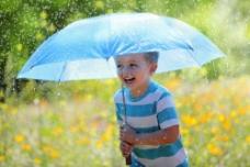 在雨中撑着伞的小男孩图片