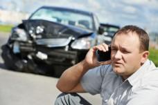 损毁的轿车与打电话的男人图片